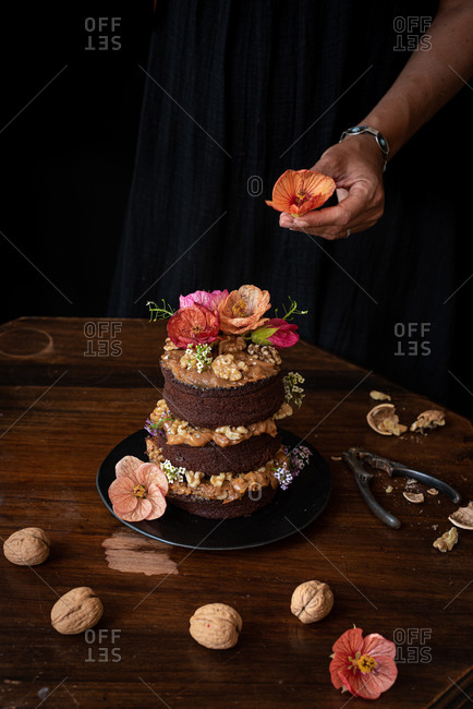Crop anonymous chef decorating festive rustic chocolate naked cake with walnuts and natural edible flowers