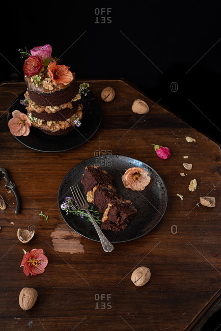 Piece of delectable chocolate naked cake with cream and walnuts garnished with fresh flowers served on wooden table