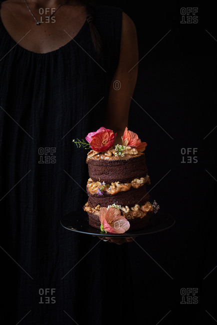 Anonymous woman carrying tray with festive rustic chocolate naked cake with cream and walnuts decorated with fresh natural pink flowers
