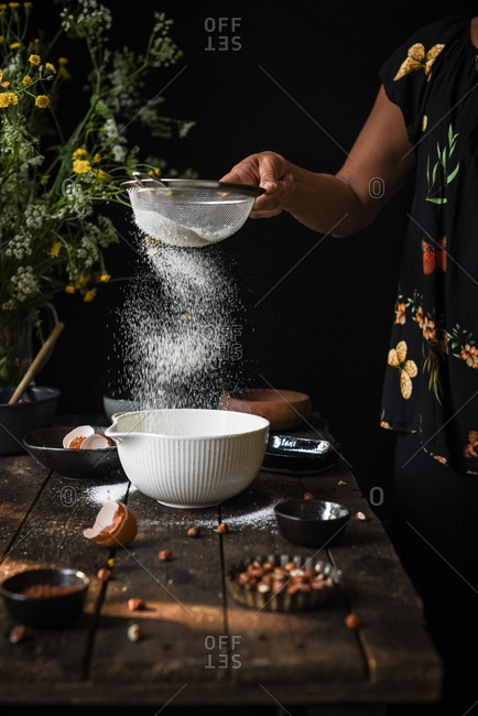 Crop anonymous female sieving flour into bowl while preparing dough for pastry at wooden table