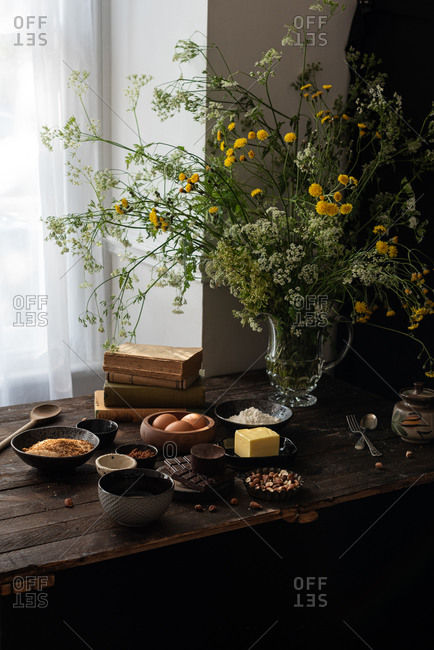 Set of various ingredients for sweet chocolate pastry recipe arranged on wooden table with fresh flowers in vase near window