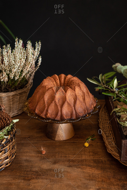 Delicious homemade bundt cake placed on rustic wooden table near wicker basket with flowers