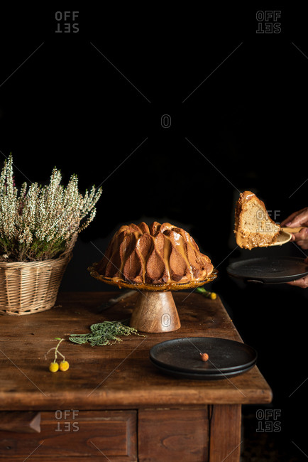 Crop person serving piece of delicious homemade bundt cake placed on rustic wooden table near wicker basket with flowers