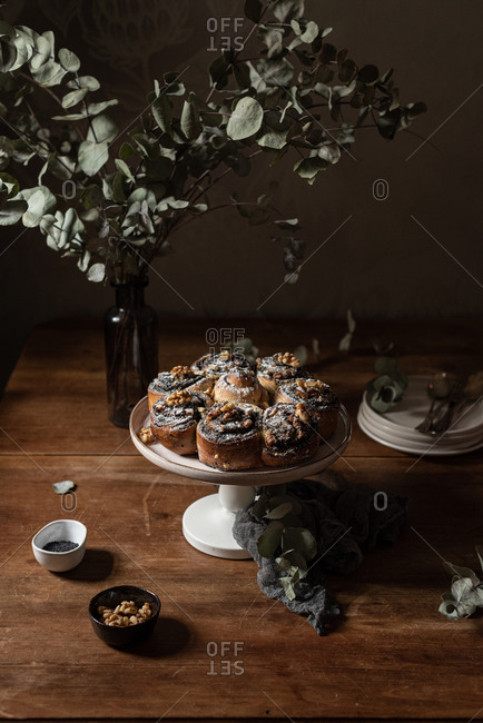 High angle of delicious homemade sweet roll buns with poppy seeds served on stand placed near vase with fresh green plants on wooden table