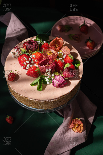 From above of yummy sweet whole rustic cake decorated with fresh ripe strawberries and flower buds served on table
