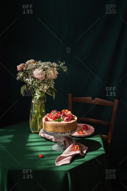 Still life composition with delicious homemade rustic cake decorated with fresh berries and flowers served on table near glass vase with delicate rose bouquet against black background