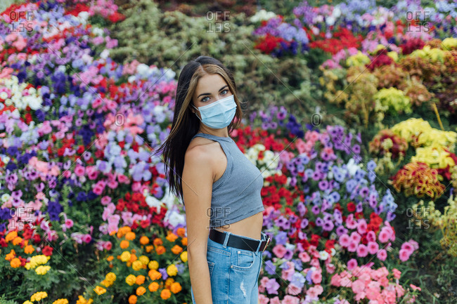 Side view of modern young female in casual outfit and protective disposable mask looking at camera while standing in summer park against colorful blooming flowers