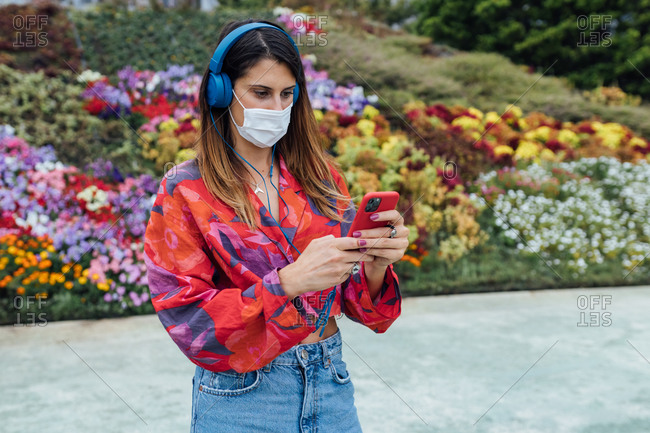 Trendy millennial female student in stylish casual outfit and medical mask with headphones communicating via mobile phone while standing in summer park with blooming flowers