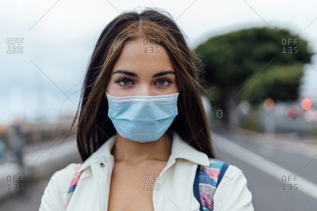 Serious millennial female in disposable medical mask looking at camera while standing on street during coronavirus pandemic