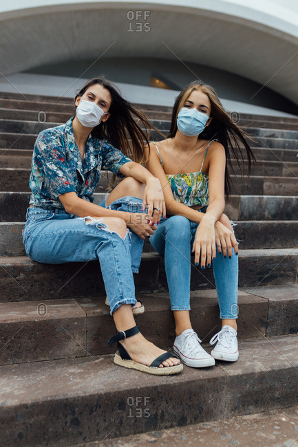 Full length of positive young hipster female friends in casual outfits and protective masks looking at camera while sitting together on stone stairs near urban building