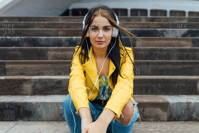 Low angle of young female in trendy jacket and ripped jeans looking at camera while sitting on stairs near urban building and listening to music through headphones