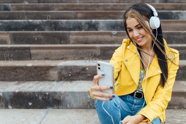 Joyful millennial woman in trendy colorful outfits and headphone sitting on stone stairs and taking selfie on smartphone while spending time together in city
