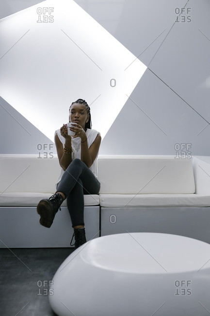 Calm African American female sitting on sofa in lobby of hotel in futuristic style while relaxing and drinking coffee