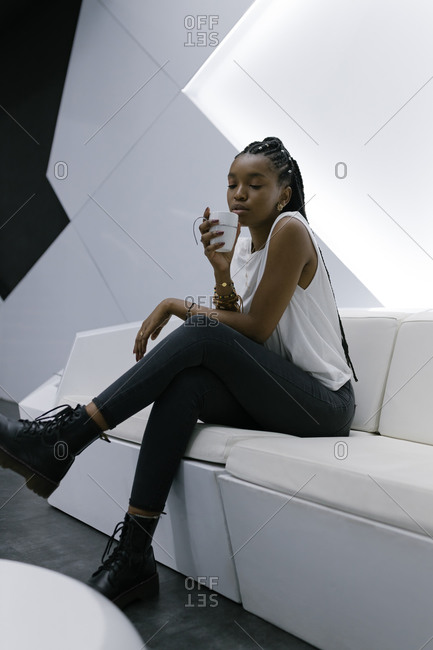 Calm African American female sitting on sofa in lobby of hotel in futuristic style while relaxing and drinking coffee with eyes closed