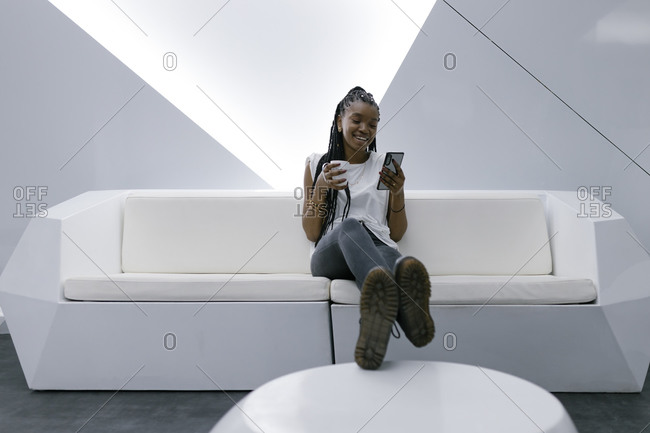 Delighted African American female sitting on sofa in room with white futuristic interior and chatting on social media on smartphone