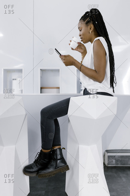 Side view of ethnic female relaxing on stool of unusual geometric shape and messaging on cellphone while drinking coffee in kitchen with white futuristic interior