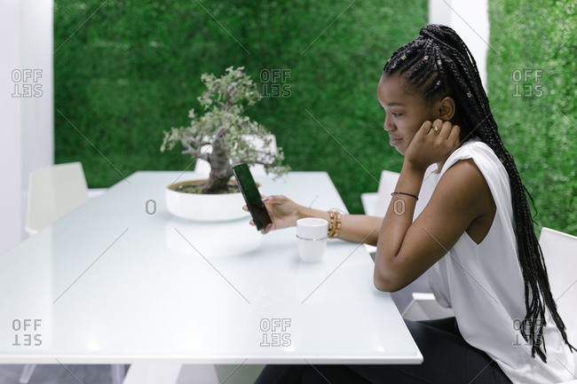 Side view of relaxed black female sitting at table in dining room with futuristic design and white furniture while browsing smartphone and drinking coffee