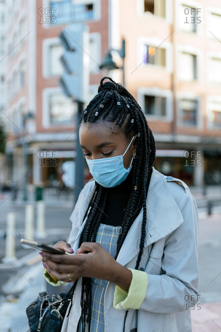 Modern young African American female in medical mask for coronavirus prevention standing on urban street and messaging on mobile phone