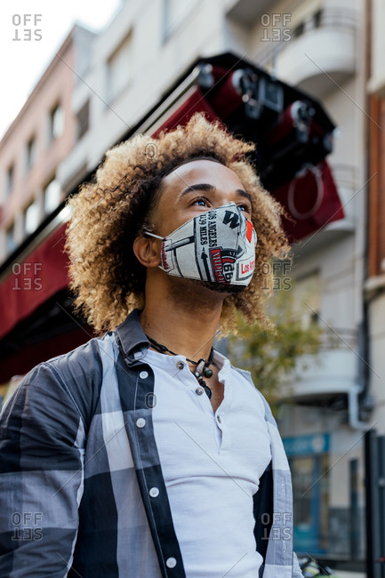 From below modern stylish African American male with curly hair dressed in trendy informal clothes and protective mask standing against blurred urban environment and looking away