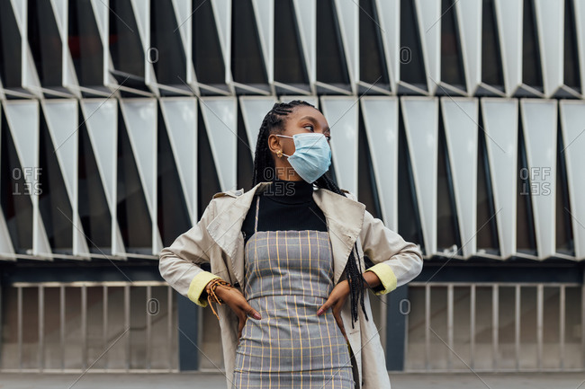 Low angle of confident young African American female in casual outfit and disposable protective mask looking away while standing against wall of modern urban building