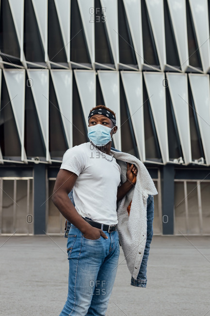 Serious African American male in casual wear with headband and protective mask looking away while standing against modern building on city street