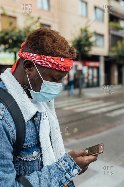 Side view of young African American hipster male in denim jacket and headband with disposable medical mask for coronavirus prevention checking messages on mobile phone while standing on city street