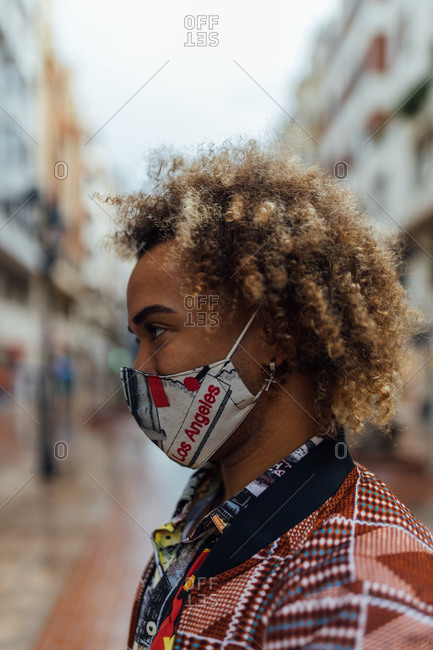 Side view of modern stylish African American male with curly hair dressed in trendy colorful informal clothes and protective mask standing against blurred urban environment and looking away