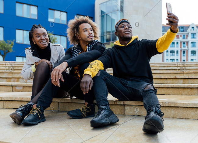 Full length of group of positive young African American students in casual clothes sitting on stairs on city street and taking selfie on mobile phone