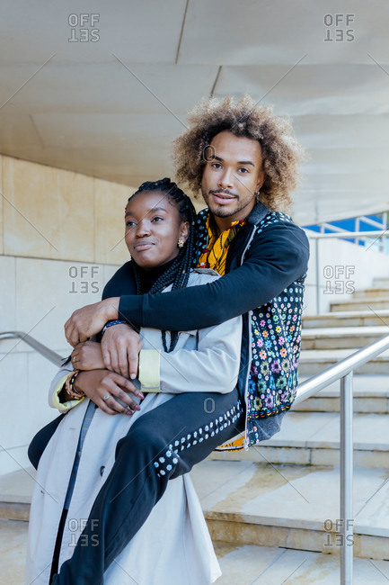 Happy young African American man embracing happy girlfriend while sitting on stairway rail near modern buildings during romantic date in city