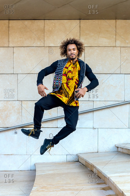 Full body of energetic young African American male in informal trendy outfit leaping on stairway against stone wall