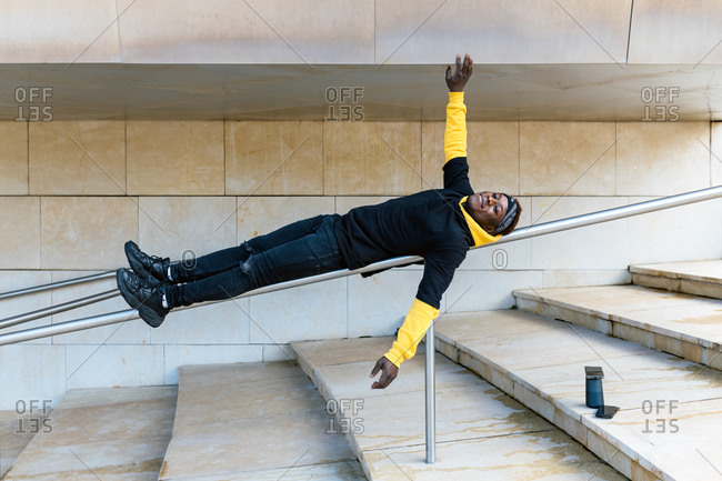 Full body of cheerful young African American hipster male in casual outfit having fun while lying on metal railing near stone stairs with arms outstretched