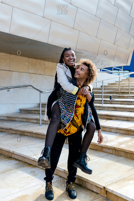 Full body of cheerful young black guy piggybacking happy girlfriend while having fun together on stone stairway near modern city building