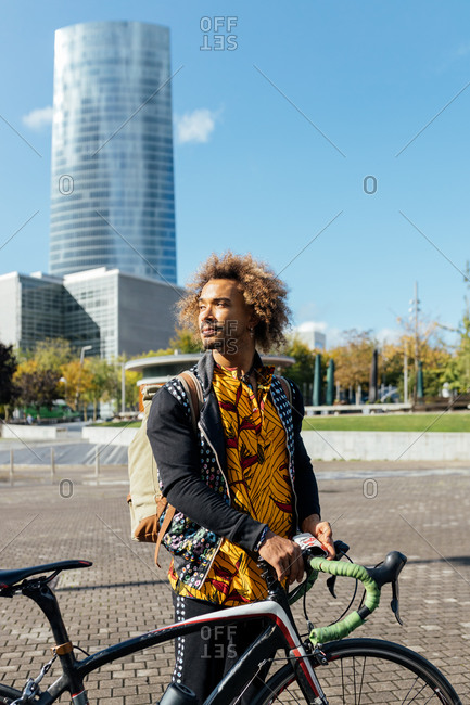 Young hipster curly haired African American male in trendy wear with backpack standing with bike on city square against modern high building and looking away
