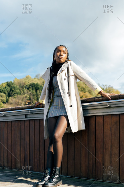 Low angle full body of young African American female in stylish casual coat leaning against fence and looking away thoughtfully while standing on bridge in autumn day