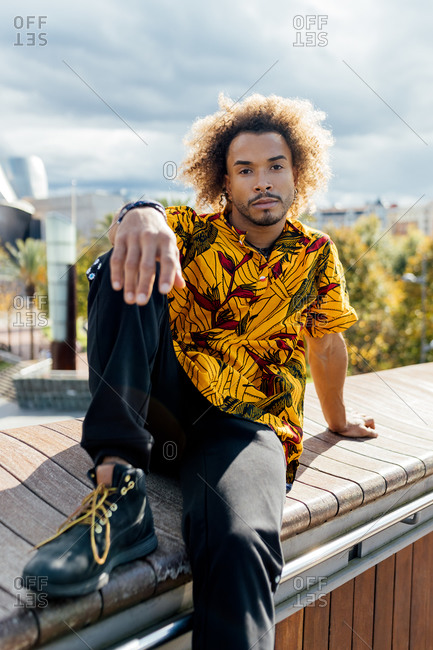 Young bearded African American hipster guy with curly Afro hair dressed in stylish colorful shirt and black jeans looking at camera while sitting on border against blurred urban background