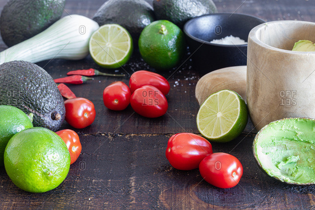 Fresh avocado and lime with tomatoes placed on wooden table with green onion and spices for traditional Mexican guacamole recipe