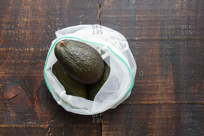 From above fresh green whole avocado on sack placed on rustic wooden table