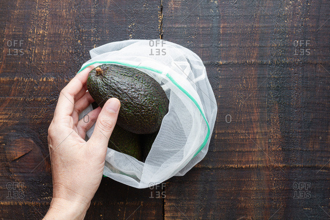 Top view of crop anonymous person taking fresh green whole avocado from sack placed on rustic wooden table while preparing healthy food
