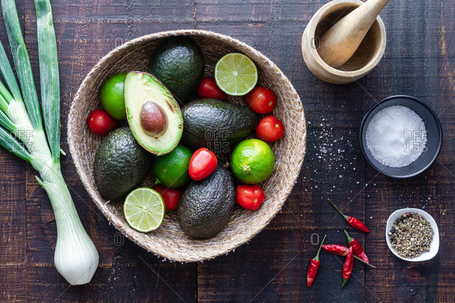 Top view bowl with fresh avocado and lime with tomatoes placed on wooden table with green onion and spices for traditional Mexican guacamole recipe