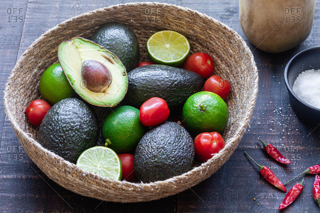 Top view bowl with fresh avocado and lime with tomatoes placed on wooden table with spices for traditional Mexican guacamole recipe