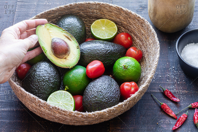 From above of crop anonymous person taking half of avocado from bowl with fresh ingredients while preparing traditional Mexican guacamole
