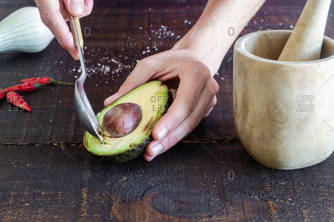 From above of crop anonymous housewife with spoon taking seed from halved avocado while preparing guacamole on table with pestle and mortar