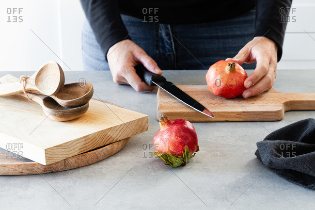 Crop anonymous male cook holding knife and whole fresh pomegranate on wooden cutting board while preparing healthy dish in kitchen