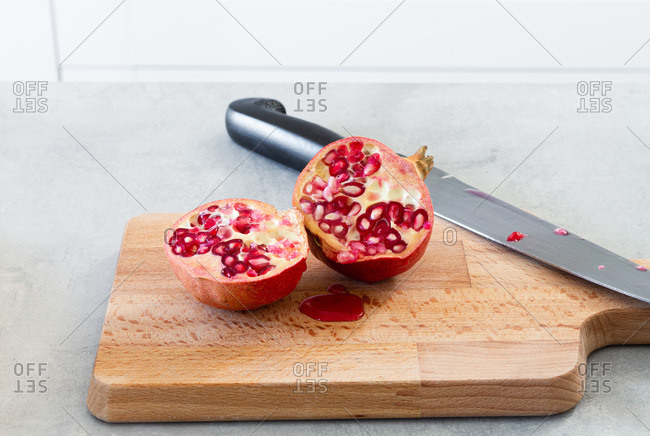 Whole and halved fresh ripe juicy pomegranate on kitchen table with cutting board and knife