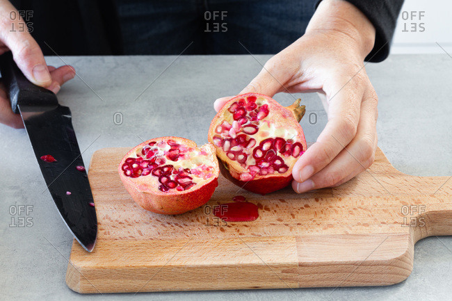 Cropped unrecognizable cook hands with knife cutting in halved fresh ripe juicy pomegranate on kitchen table in cutting board
