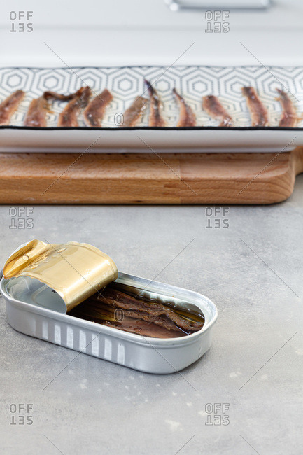 High angle of open metal can with fish conserves placed on table during food preparation