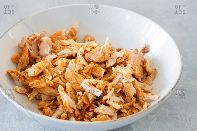 High angle of white bowl with shredded grilled chicken meat for Caesar salad on gray table