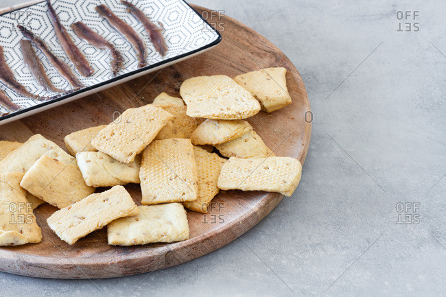 Heap of crispy salt crackers served on wooden board near plate with canned fish as appetizer