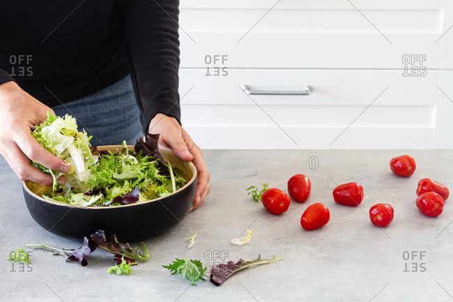 Faceless person mixing salad green leaves in bowl with hand at table with fresh tomatoes for Ceasar salad