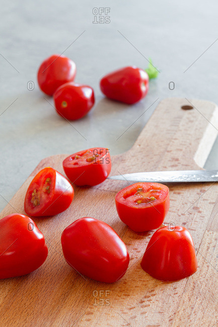 Wooden cutting board with cut juicy cherry tomatoes prepared for Caesar salad on counter